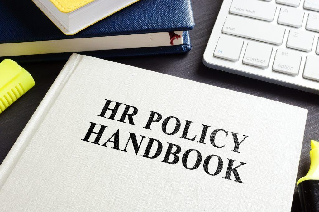 Hr Policy Handbook On An Office Desk.